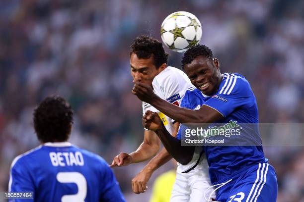 Igor de Camargo of Moenchengladbach and Taye Taiwo of Kiew go up for a header during the UEFA Champions League playoff first leg match between...