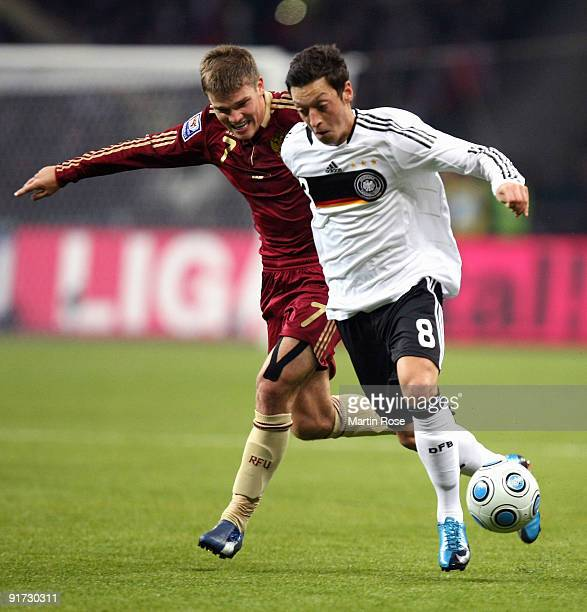 Igor Denisov of Russia and Mesut Oezil of Germany battle for the ball during the FIFA 2010 World Cup Group 4 Qualifier match between Russia and...
