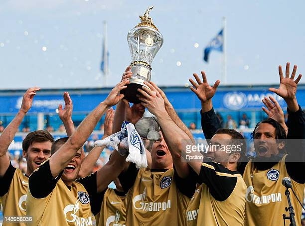 Igor Denisov, Vyacheslav Malafeev and Alexandr Kerzhakov of FC Zenit St. Petersburg hold champions cup after the Russian Football League Championship...