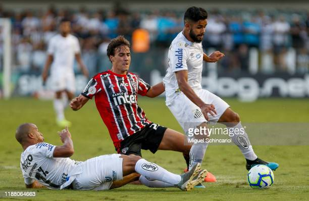 Igor Gomes of Sao Paulo vies the ball with Carlos Sanchez and Felipe Jonathan of Santos during a match between Santos and Sao Paulo for the...