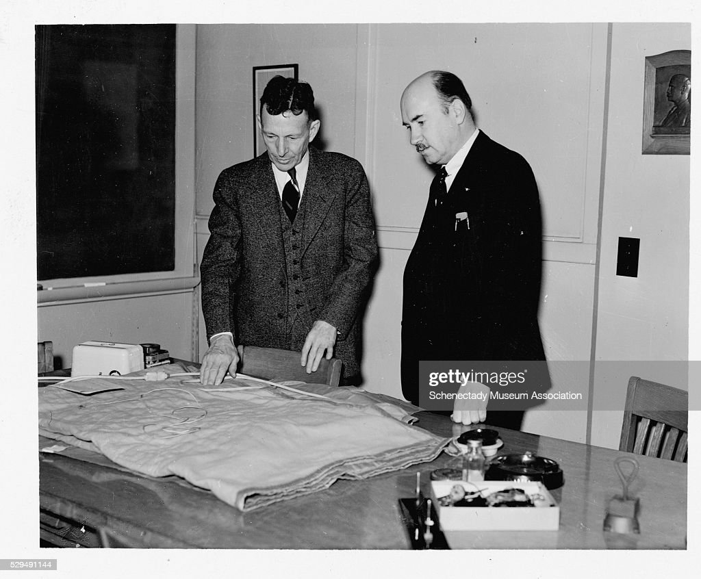 Men Looking at an Electric Blanket : News Photo