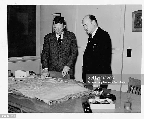 Igor I Sikorsky developer of the helicopter listens as Dr WD Coolidge talk about an electric blanket that was developed by General Electric