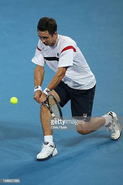 Igor Kunitsyn of Russia plays a backhand during his match against Lleyton Hewitt of Australia on day three of the Brisbane International at Pat...