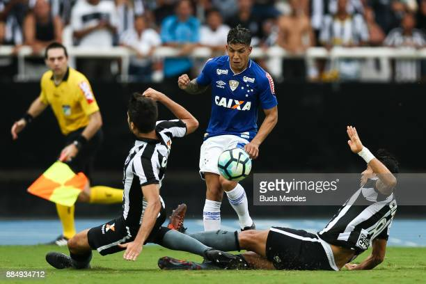 Igor Rabello and Dudu Cearense of Botafogo struggle for the ball with Lucas Romero of Cruzeiro during a match between Botafogo and Cruzeiro as part...