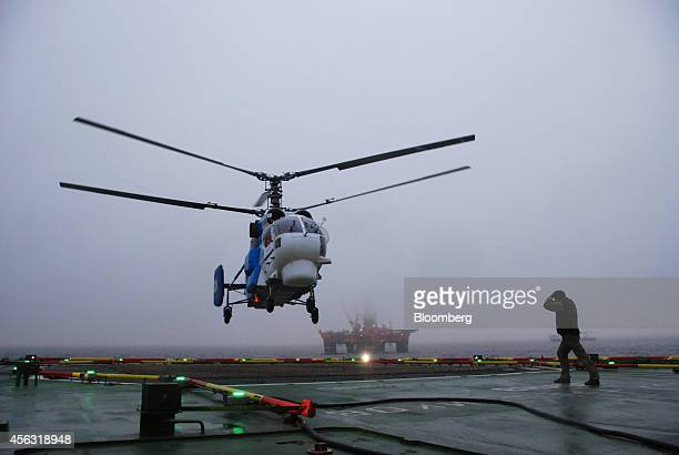 Igor Sechin chief executive officer of OAO Rosneft returns by helicopter to the polar research vessel Akademik Tryoshnikov following a trip to the...