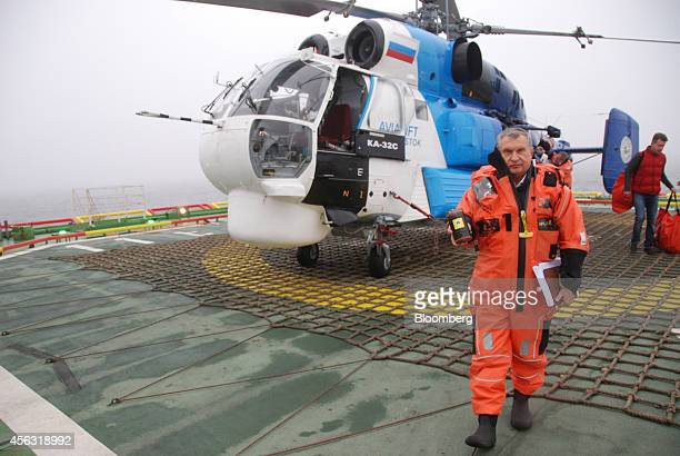 Igor Sechin chief executive officer of OAO Rosneft returns to the polar research vessel Akademik Tryoshnikov carrying a sample of oil from the West...