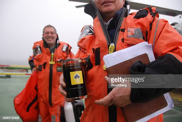 Igor Sechin chief executive officer of OAO Rosneft right returns to the polar research vessel Akademik Tryoshnikov carrying a sample of oil from the...