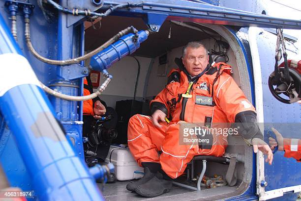 Igor Sechin chief executive officer of OAO Rosneft wears an immersion suit as he sits aboard a helicopter on the polar research vessel Akademik...