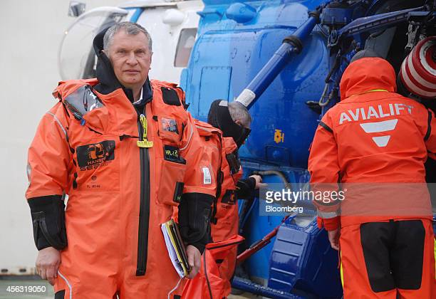 Igor Sechin chief executive officer of OAO Rosneft wears an immersion suit as he prepares to board a helicopter aboard the polar research vessel...