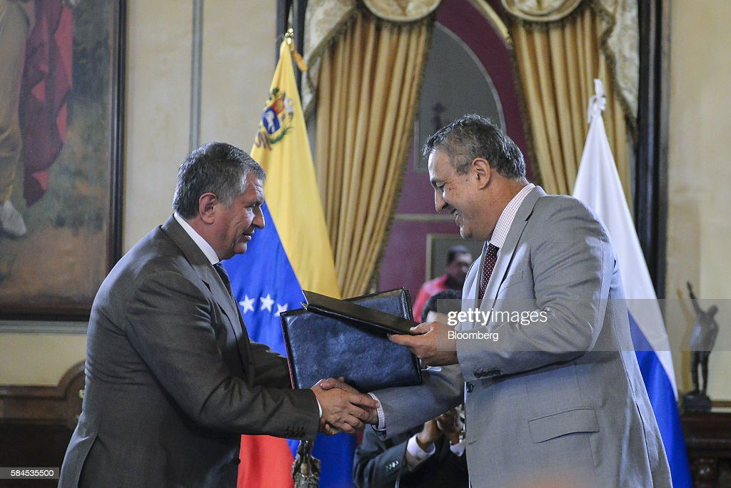 Igor Sechin, chief executive officer of Rosneft PJSC, left, and Eulogio del Pino, president of Petroleos de Venezuela SA (PDVSA) shake hands after signing natural gas deals in Caracas, Venezuela, on Thursday, July 28, 2016. The agreements included a deal for Rosneft to participate in the Mariscal Sucre natural gas project. Photographer: Carlos Becerra/Bloomberg via Getty Images