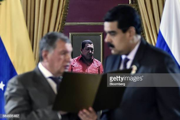 Igor Sechin chief executive officer of Rosneft PJSC left holds a document while speaking with Nicolas Maduro president of Venezuela in front of a...