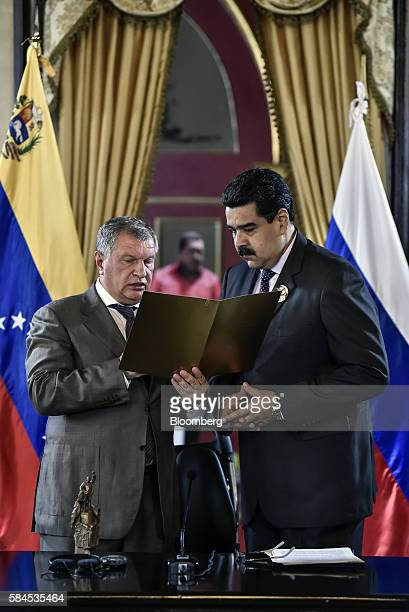Igor Sechin chief executive officer of Rosneft PJSC left holds a document while speaking with Nicolas Maduro president of Venezuela after Rosneft...