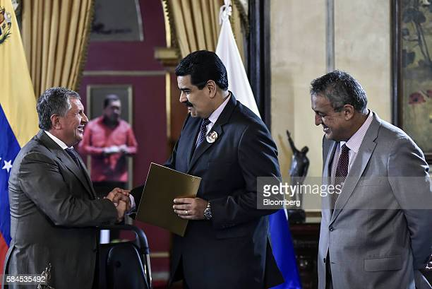 Igor Sechin chief executive officer of Rosneft PJSC left shakes hands with Nicolas Maduro president of Venezuela center as Eulogio del Pino president...