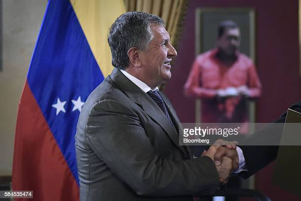 Igor Sechin chief executive officer of Rosneft PJSC shakes hands with Nicolas Maduro president of Venezuela not pictured after signing natural gas...