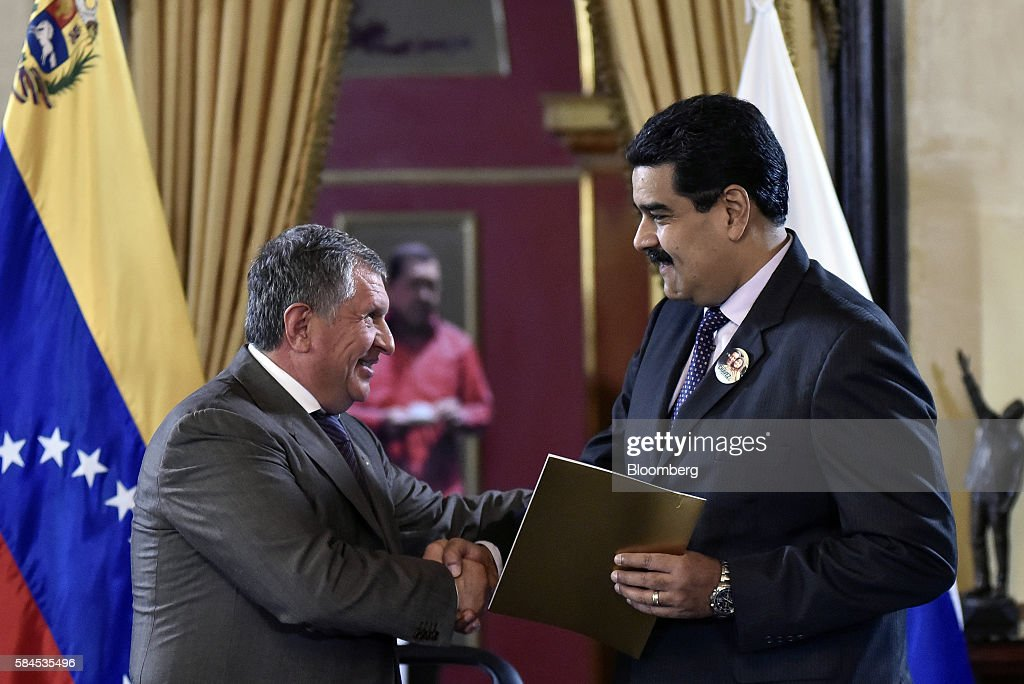 Igor Sechin, chief executive officer of Rosneft PJSC, shakes hands with Nicolas Maduro, president of Venezuela, after signing natural gas deals with Petroleos de Venezuela SA (PDVSA) in Caracas, Venezuela, on Thursday, July 28, 2016. The agreements included a deal for Rosneft to participate in the Mariscal Sucre natural gas project. Photographer: Carlos Becerra/Bloomberg via Getty Images