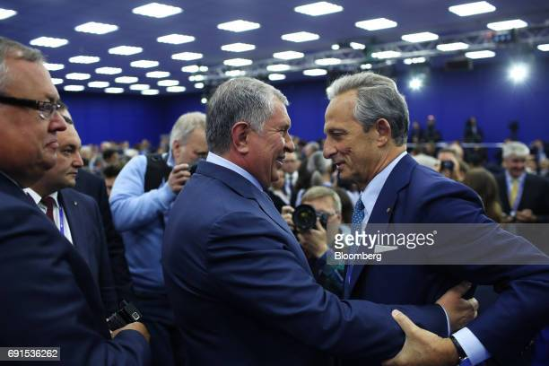 Igor Sechin president of Rosneft PJSC left greets Marco Tronchetti Provera chairman of Pirelli Tyre SpA before a panel session during the St...
