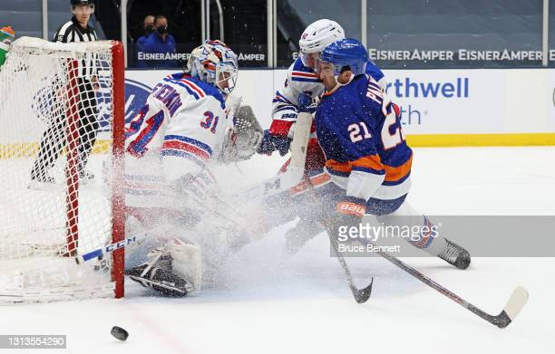 Igor Shesterkin and Brendan Smith of the New York Rangers defend against Kyle Palmieri of the New York Islanders during the second period at the...