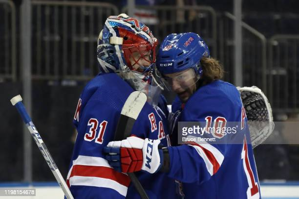 Igor Shesterkin of the New York Rangers celebrates his 53 victory in his first NHL game against the Colorado Avalanche and is hugged by Artemi...