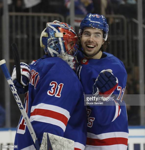 Igor Shesterkin of the New York Rangers celebrates his 53 victory in his first NHL game against the Colorado Avalanche and is hugged by Filip Chytil...