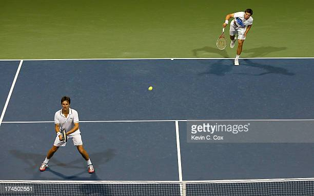 Igor Sijsling of the Netherlands and Edouard Roger-Vasselin of France serve to Santiago Giraldo of Columbia and Ricardas Berankis of Lithuania during...
