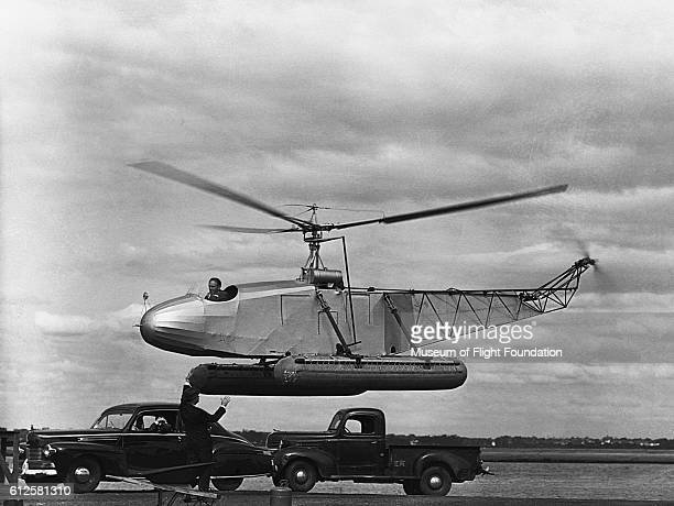 Igor Sikorsky instructs pilot Les Morris during a hover test in the VS300 helicopter prototype in the early 1940's