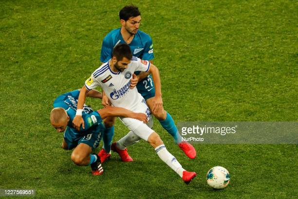 Igor Smolnikov and Magomed Ozdoev of Zenit Saint Petersburg vie for the ball with Artem Kulishev of Orenburg during the Russian Premier League match...