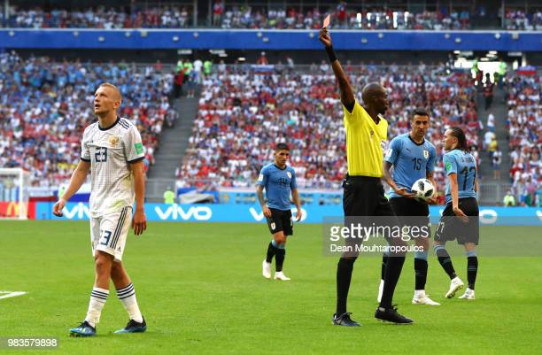 Igor Smolnikov of Russia is shown his second yellow card by referee Antonio Malang Diedhiou during the 2018 FIFA World Cup Russia group A match...