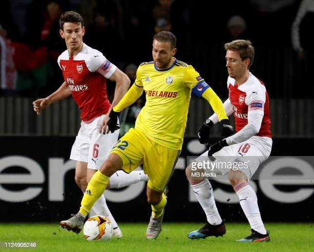 Igor Stasevich of FC BATE Borisov vies for the ball with Laurent Koscielny and Nacho Monreal of Arsenal during the UEFA Europa League Round of 32...