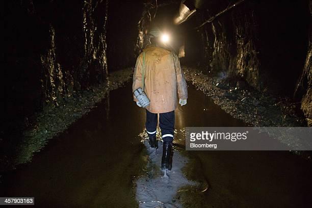 Igor Tazarachev a mining engineer walks through water as he inspects underground works at the OAO Alrosa diamond mine in Udachny Sakha Republic...