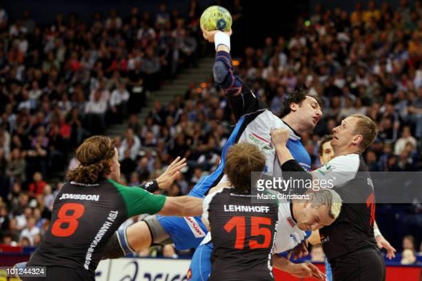 Igor Vori and Pascal Hens of HSV Handball rise above Hannes Jon Johannson, Lars Lehnhoff and Adrius Stelmokas of TSV Hannover to shoot at goal during...
