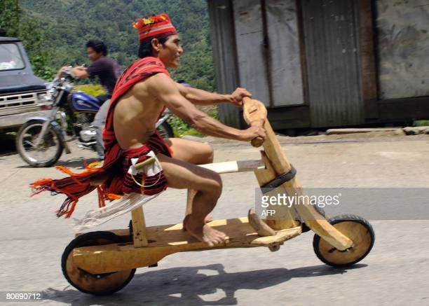 Igorot tribesman Robert Duyugan rides his wooden scooter in the northern mountainous town of Banaue during a competition on April 16 2008 as the town...