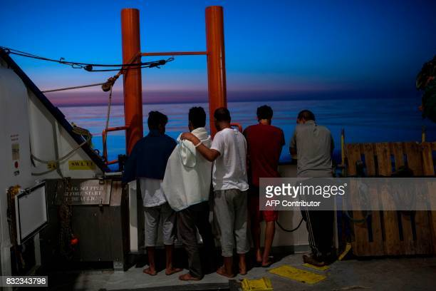 TOPSHOT igrants watch sunrise on the deck of the Aquarius rescue ship run by NGO SOS Mediterranee and Medecins Sans Frontieres after their transfer...