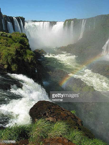 Iguazu Falls in Argentina with a rainbow and grassy hills