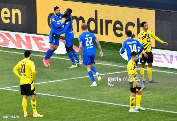Ihlas Bebou of TSG 1899 Hoffenheim celebrates with teammate Munas Dabbur after scoring his team's second goal, as Emre Can, Raphael Guerreiro, and...