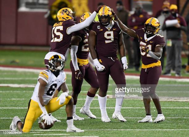 Ihmir Smith-Marsette of the Iowa Hawkeyes looks on as Esezi Otomewo of the Minnesota Golden Gophers celebrates a tackle during the second quarter of...