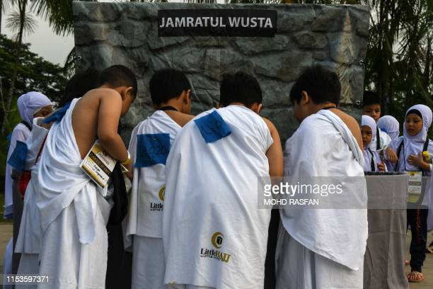 Ihramclad Muslim boys throw mock stones made from papier mache while performing the ritual of stoning the devil during an educational simulation of...