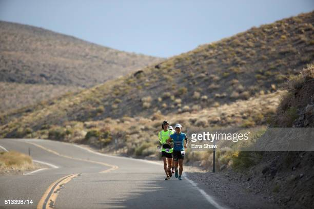 Iino Wataru of Japan runs with a member of his support team during the STYR Labs Badwater 135 on July 11 2017 in Death Valley California Wataru went...