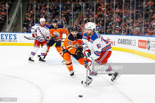Iiro Pakarinen of the Edmonton Oilers harasses David Desharnais of the New York Rangers at Rogers Place on March 3 2018 in Edmonton Canada