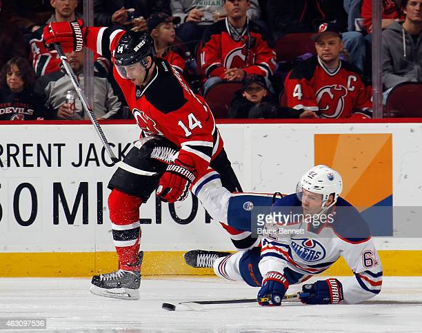 Iiro Pakarinen of the Edmonton Oilers is tripped up by Adam Henrique of the New Jersey Devils during the second period at the Prudential Center on...
