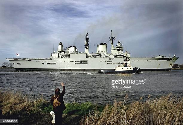 A passerby waves to the English aircraft carrier HMS Ark Royal as it enters Ijmuiden 09 March 2007 The gigantic navy vessel carries 690 men and women...
