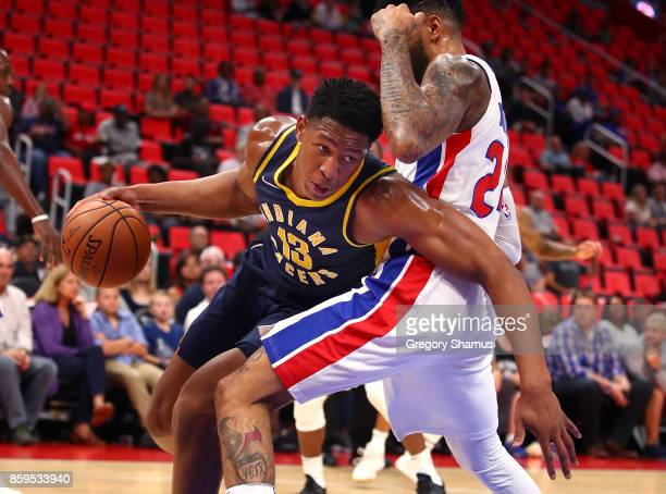 Ike Anigbogu of the Indiana Pacers tries to drive around Eric Moreland of the Detroit Pistons during a pre season game at Little Caesars Arena on...