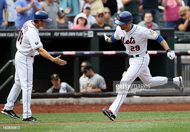 Ike Davis of the New York Mets celebrates with third base coach Tim Teufel after hitting a home run against the Pittsburgh Pirates at Citi Field on...