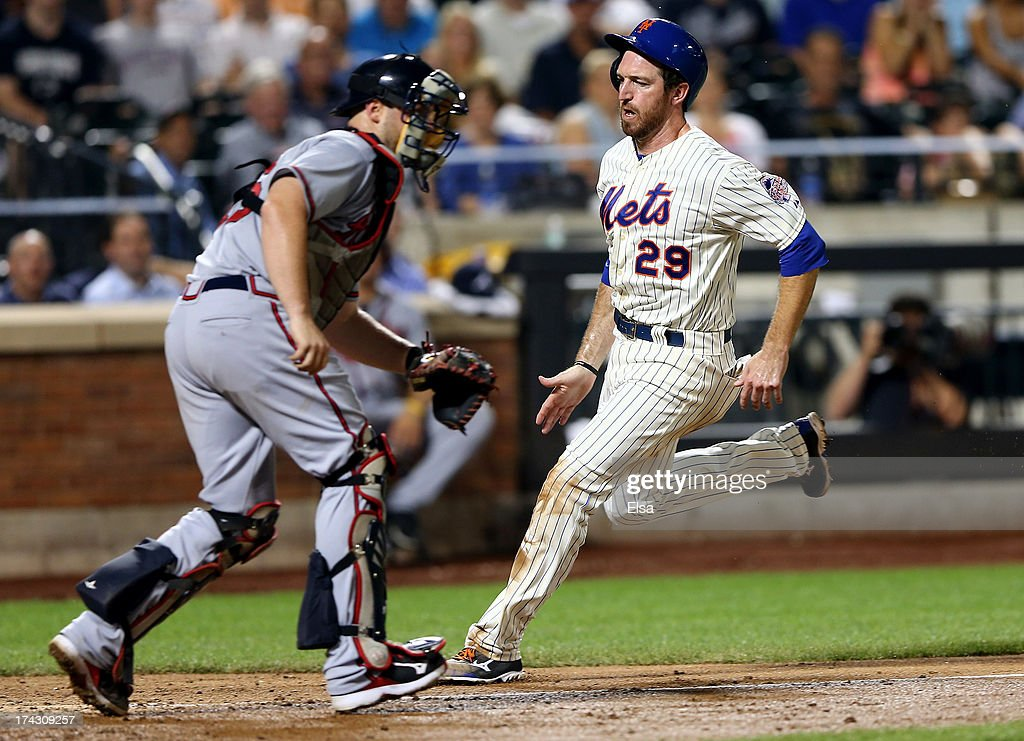 Ike Davis #29 of the New York Mets scores a run as Brian McCann #16 of the Atlanta Braves is unable to make the tag in the sixth inning on July 23, 2013 at Citi Field in the Flushing neighborhood of the Queens borough of New York City.