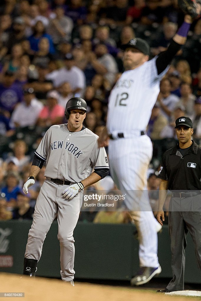 Ike Davis #24 of the New York Yankees stands on first base after hitting an eighth inning RBI single against the Colorado Rockies as Mark Reynolds #12 of the Colorado Rockies leaps to cutoff a throw during a regular season interleague game at Coors Field on June 14, 2016 in Denver, Colorado.