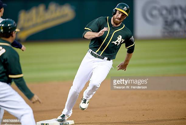 Ike Davis of the Oakland Athletics rounds third base to score on an rbi single from Stephen Vogt against the Seattle Mariners in the bottom of the...