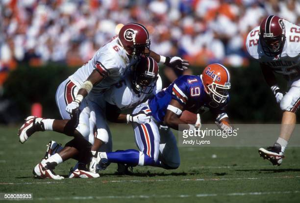 Ike Hilliard of the Florida Gators is tackled by Terry Cousin and Ben Washington of the South Carolina Gamecocks on November 16 1996 at Ben Hill...