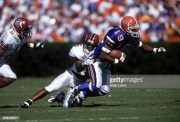 Ike Hilliard of the Florida Gators is tackled by Terry Cousin of the South Carolina Gamecocks on November 16 1996 at Ben Hill Griffin Stadium in...