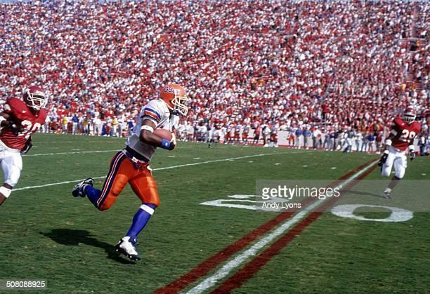 Ike Hilliard of the Florida Gators runs with the ball against the Arkansas Razorbacks on October 5, 1996 at Razorback Stadium in Fayetteville,...
