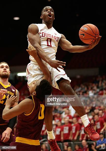 Ike Iroegbu of the Washington State Cougars goes to the basket over defender Tra Holder of the Arizona State Sun Devils in the first half at Beasley...