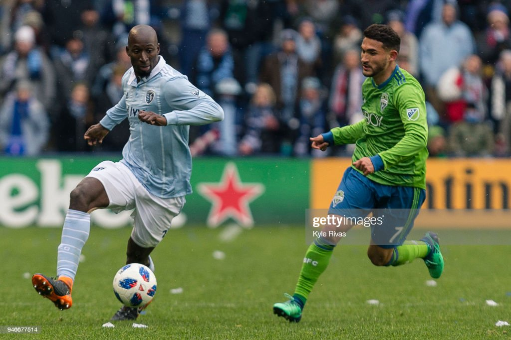 Ike Opara #3 of Sporting Kansas City pushes past Cristian Roldan #7 of Seattle Sounders during the second half on April 15, 2018 at Children's Mercy Park in Kansas City, Kansas.